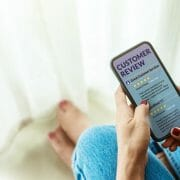 Person looking at cell phone displaying Customer Review