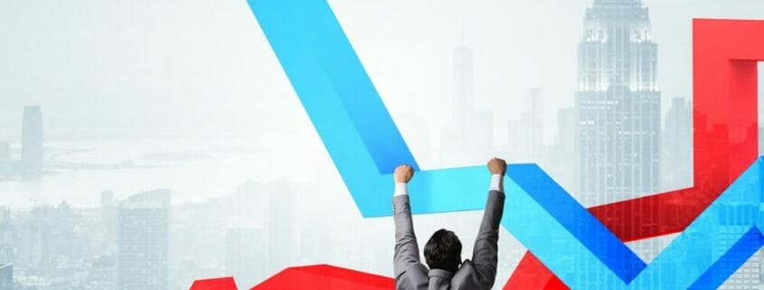 A man hanging onto the a blue up-trend arrow with a red down-trend arrow behind and the New York skyline