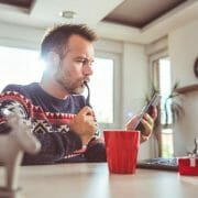 Man in Christmas Sweater looking at cell phone and laptop - to illustrate Black Friday shopping