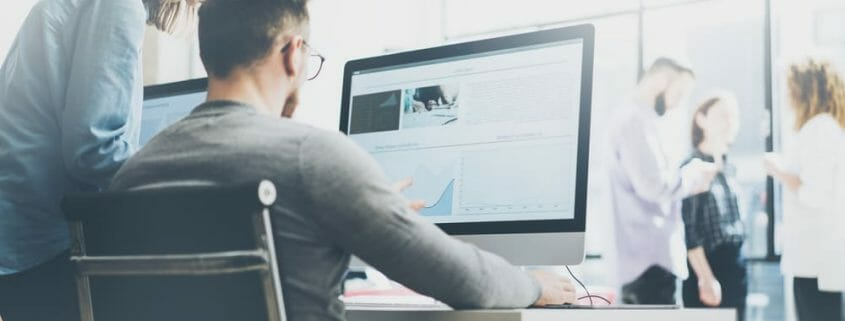 Woman looking over the shoulder of a man seated at a large computer screen