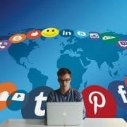 Male with a MacBook and Social Media icons swirling around him