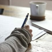 Female at a desk writing with a pen with coffee and notepad beside her