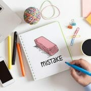 Laptop, smart phone, elastics, post-it notes, paper clips, coffee and person with highlighter on notebook that says Mistake