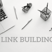 Laptop, pens, pencils, watch and eyeglasses with the words Link Building