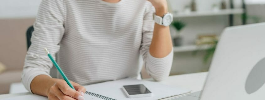 Woman with pad and pencil focused on laptop screen.