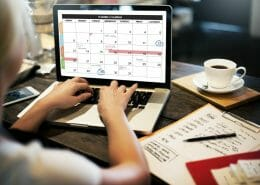 Female at a desk working with a Planner & Calendar on a laptop.